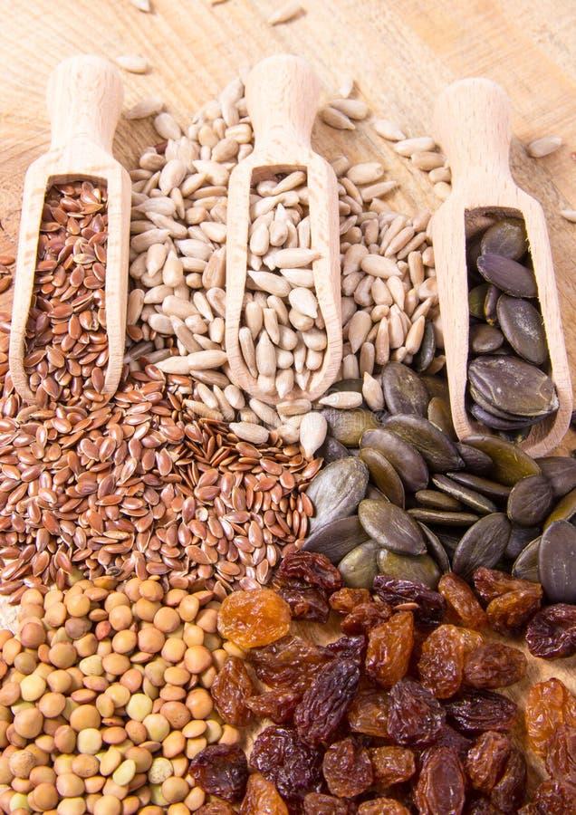 Flaxseed, κολοκύθα, σταφίδες, φακές και σπόροι ηλίανθων στα ξύλινα κουτάλια στοκ φωτογραφία με δικαίωμα ελεύθερης χρήσης