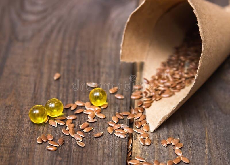 Flaxseed πετρέλαιο στα καλύμματα σε ένα ξύλινο υπόβαθρο Phytotherapy στοκ εικόνες με δικαίωμα ελεύθερης χρήσης
