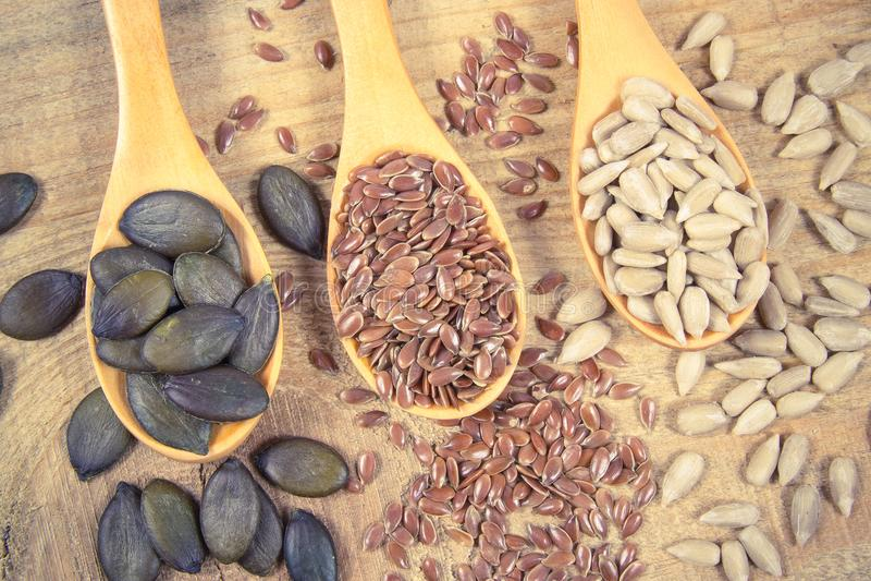 Flaxseed, bania i słonecznikowi ziarna w drewnianych łyżkach, fotografia stock