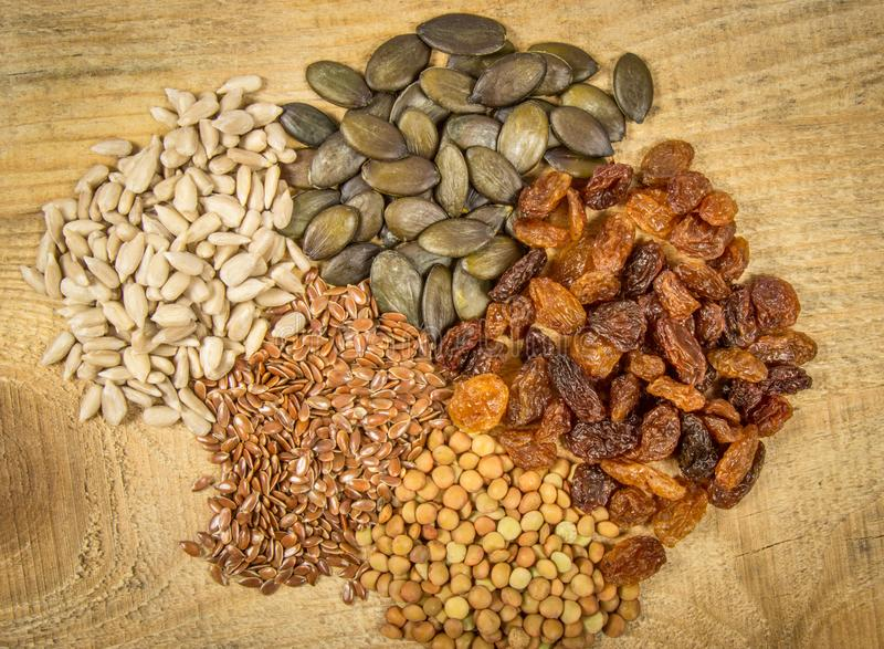 Flaxseed, bania, rodzynki, soczewicy i słonecznikowi ziarna w drewnianych łyżkach, zdjęcie royalty free