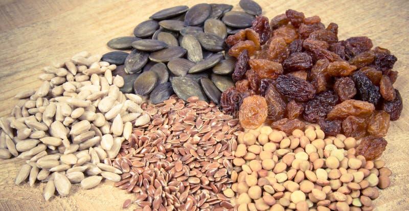 Flaxseed, bania, rodzynki, soczewicy i słonecznikowi ziarna w drewnianych łyżkach, obraz royalty free