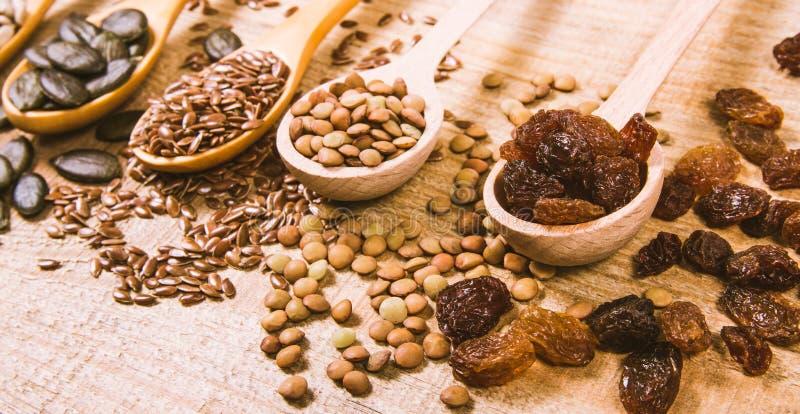 Flaxseed, bania, rodzynki, soczewicy i słonecznikowi ziarna w drewnianych łyżkach, zdjęcia royalty free