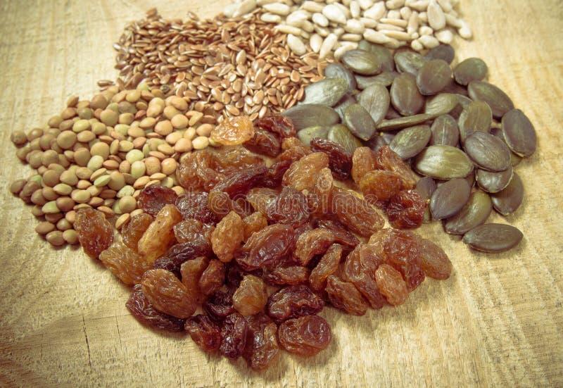 Flaxseed, bania, rodzynki, soczewicy i słonecznikowi ziarna w drewnianych łyżkach, fotografia royalty free