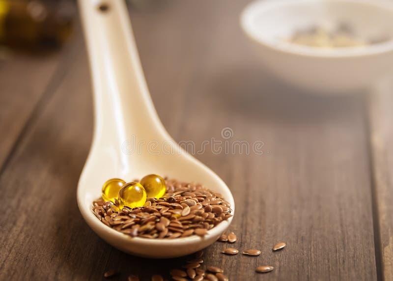 Flaxseed olej w nakrętkach na drewnianym tle Ziołolecznictwo obrazy royalty free