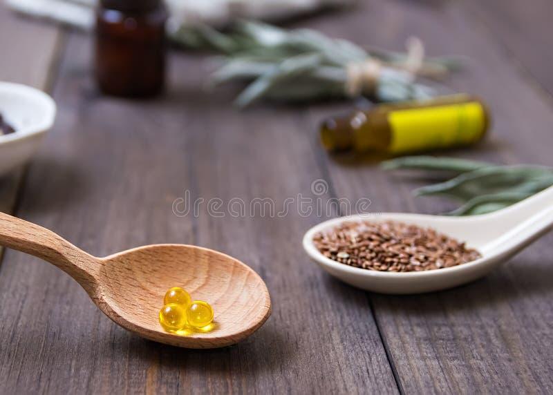 Flaxseed olej w nakrętkach na drewnianym tle Ziołolecznictwo zdjęcia stock