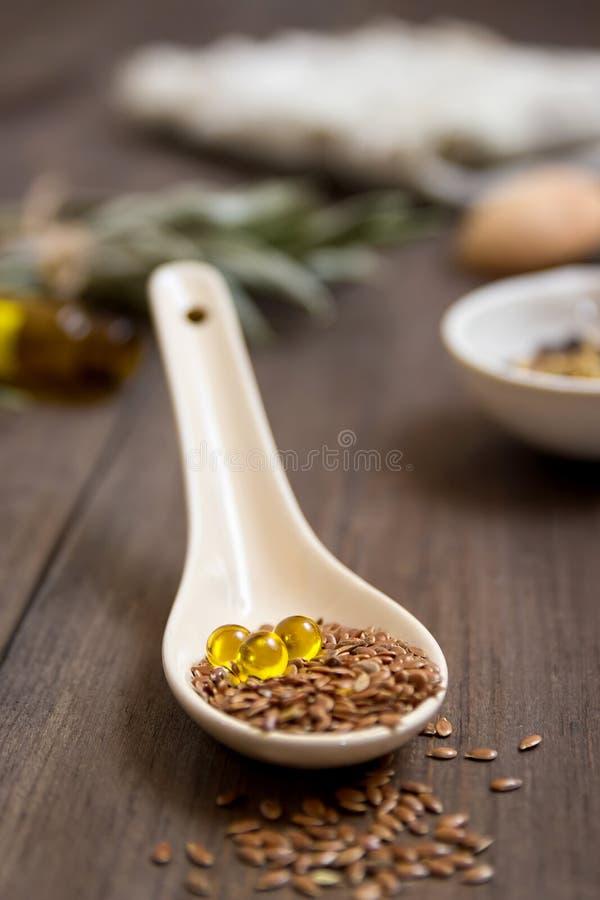 Flaxseed olej w nakrętkach na drewnianym tle Ziołolecznictwo fotografia royalty free