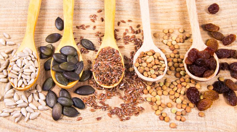 Flaxseed, pumpkin, raisins, lentils and sunflower seeds in wooden spoons. Seeds - a concept of healthy food additives royalty free stock images