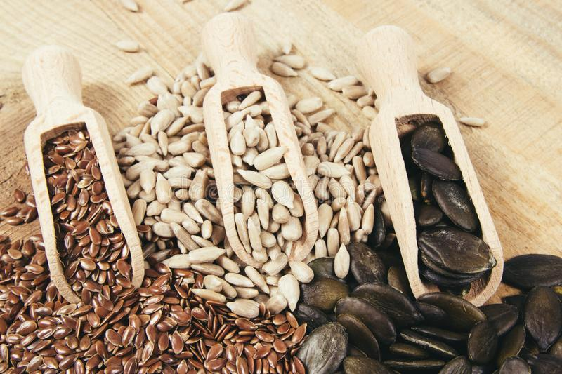 Flaxseed, pumpkin, raisins, lentils and sunflower seeds in wooden spoons. Seeds - a concept of healthy food additives royalty free stock photos