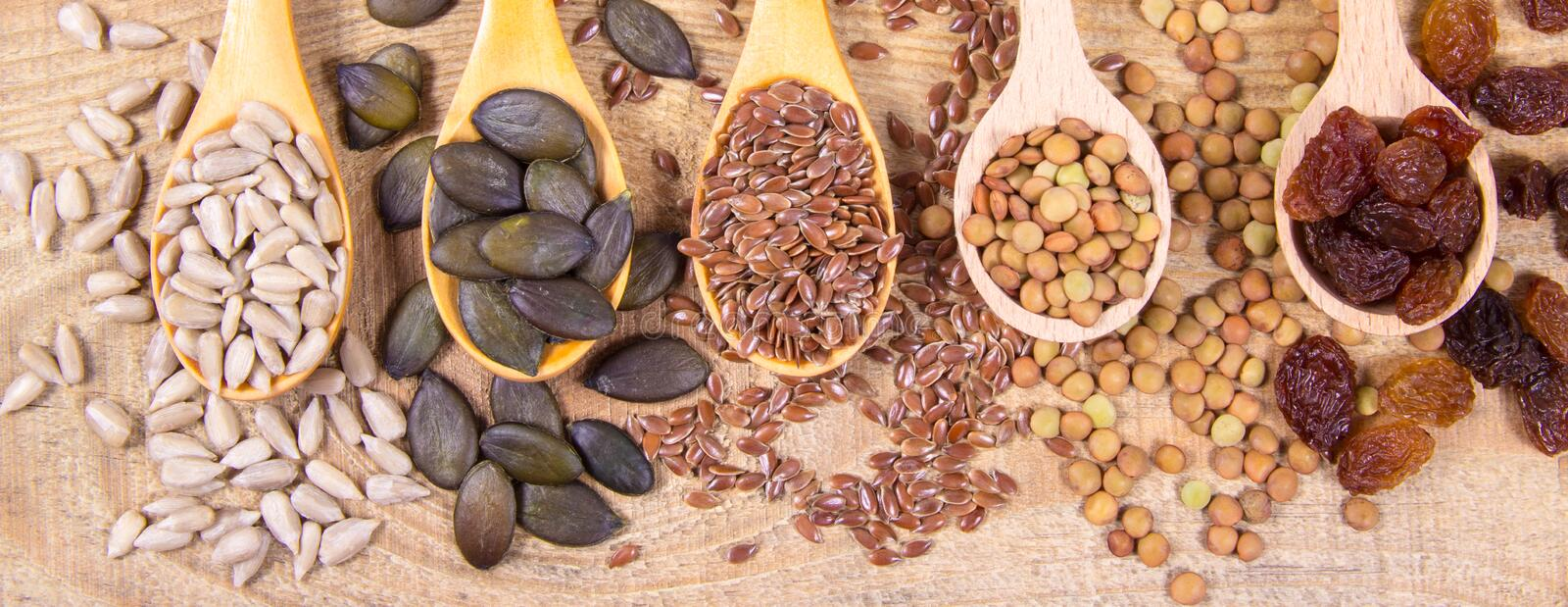 Flaxseed, pumpkin, raisins, lentils and sunflower seeds in wooden spoons. Seeds - a concept of healthy food additives stock photo