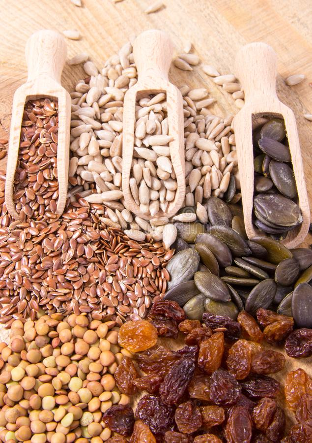 Flaxseed, pumpkin, raisins, lentils and sunflower seeds in wooden spoons. Seeds - a concept of healthy food additives royalty free stock photo