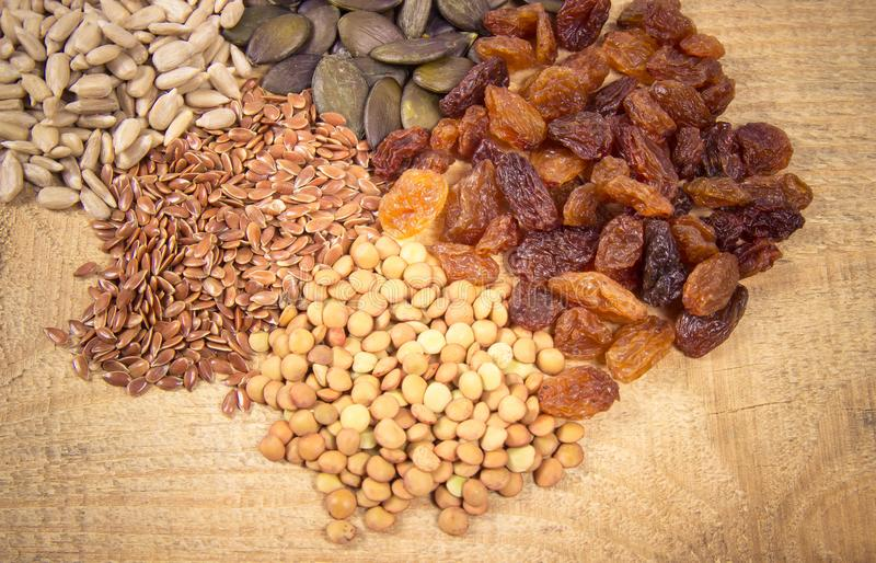 Flaxseed, pumpkin, raisins, lentils and sunflower seeds in wooden spoons. Seeds - a concept of healthy food additives stock images