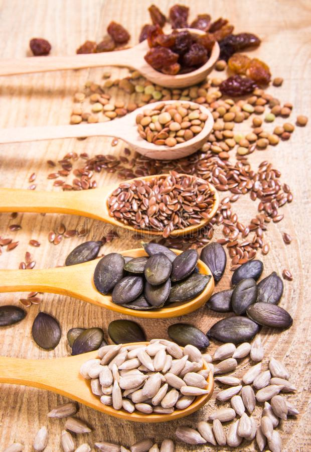 Flaxseed, pumpkin, raisins, lentils and sunflower seeds in wooden spoons. Seeds - a concept of healthy food additives royalty free stock image