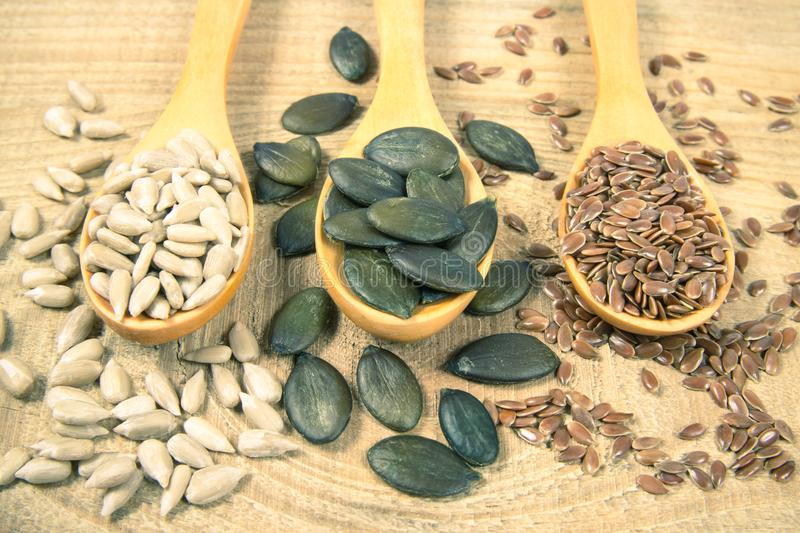 Flaxseed, pumpkin and sunflower seeds in wooden spoons. Seeds - a concept of healthy food additives stock photography
