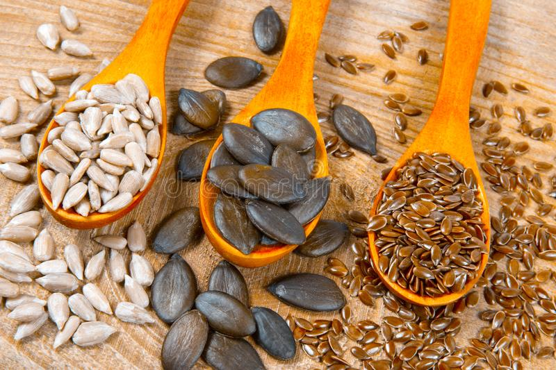 Flaxseed, pumpkin and sunflower seeds in wooden spoons. Seeds - a concept of healthy food additives royalty free stock image