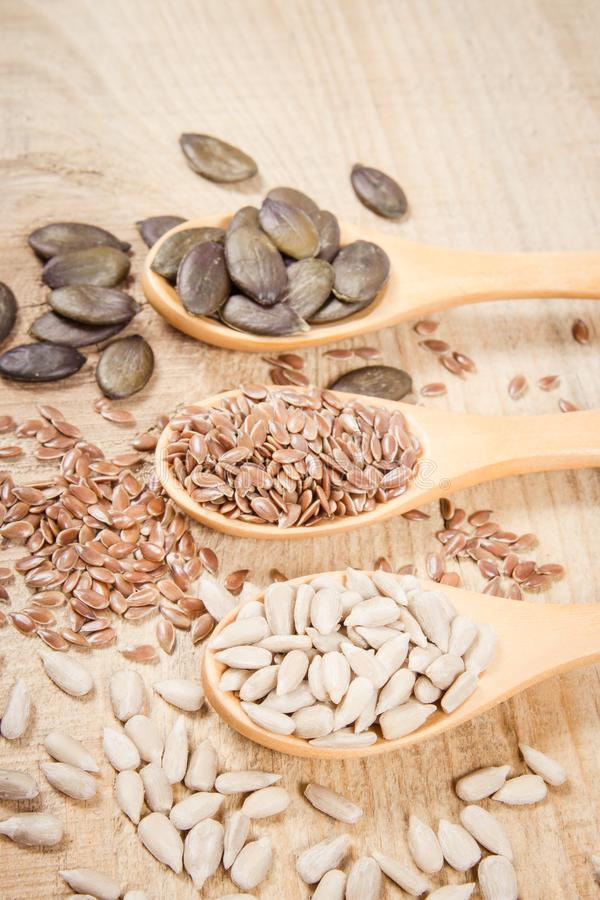 Flaxseed, pumpkin and sunflower seeds in wooden spoons. Seeds - a concept of healthy food additives royalty free stock photos