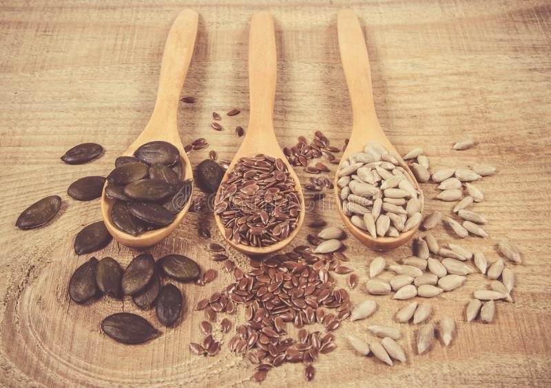 Flaxseed, pumpkin and sunflower seeds in wooden spoons. Seeds - a concept of healthy food additives royalty free stock photo