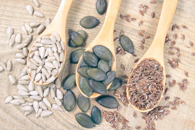 Flaxseed, pumpkin and sunflower seeds in wooden spoons. Seeds - a concept of healthy food additives stock photo