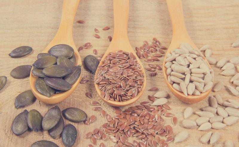 Flaxseed, pumpkin and sunflower seeds in wooden spoons. Seeds - a concept of healthy food additives stock image