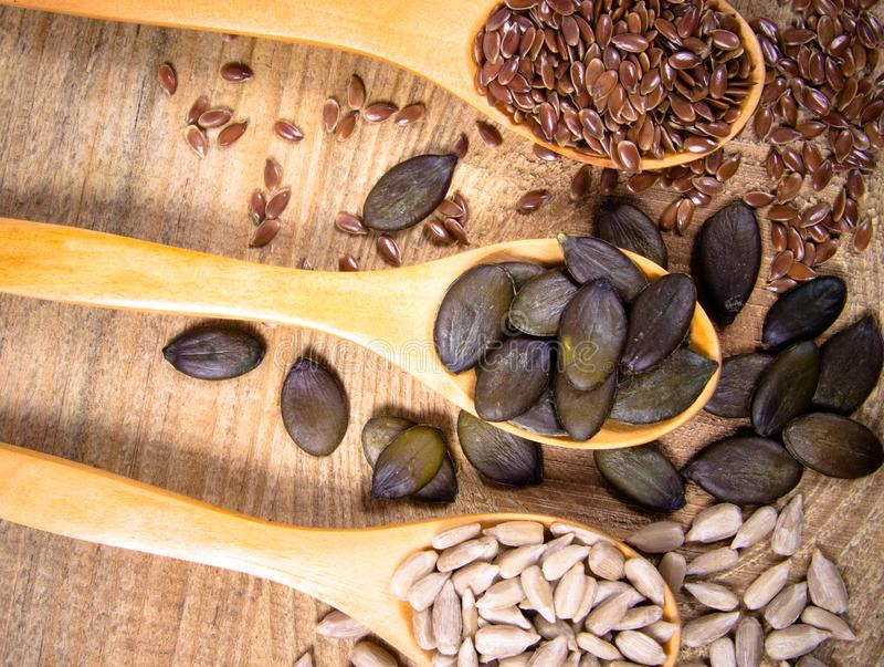 Flaxseed, pumpkin and sunflower seeds in wooden spoons. Seeds - a concept of healthy food additives royalty free stock photography