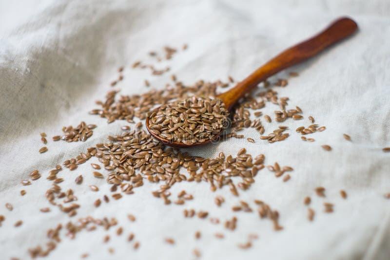 Flaxseed w drewnianej łyżce, kropiącej na bieliźnianym tablecloth obrazy stock