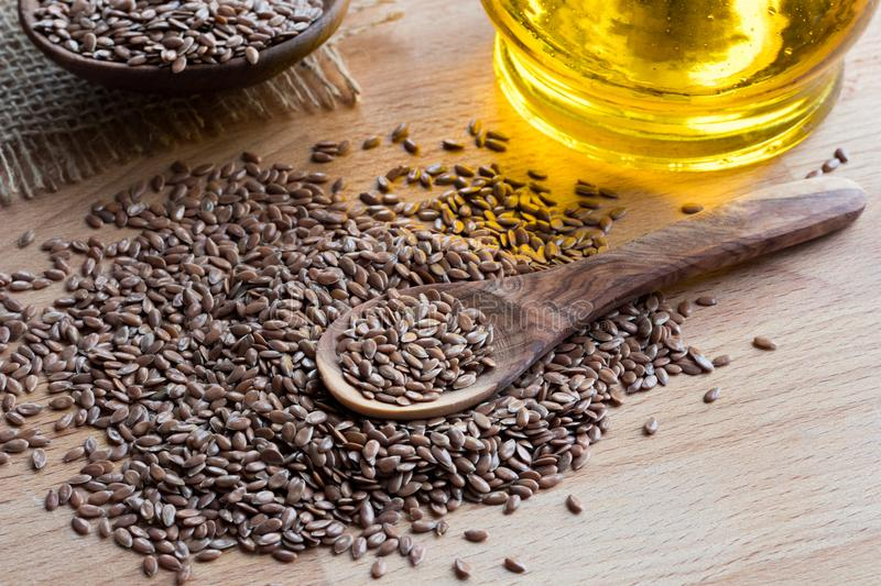 Flaxseed on a wooden spoon, with flaxseed oil in the background.  stock images