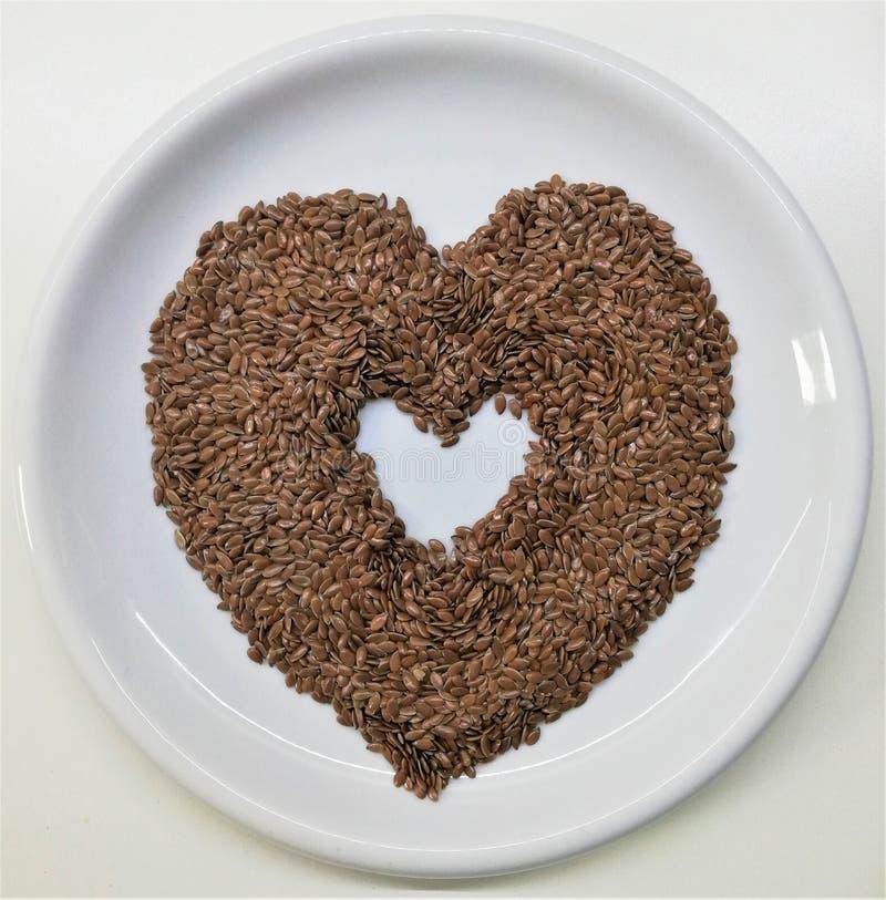 Flaxseeds de Brown sob a forma do coração foto de stock