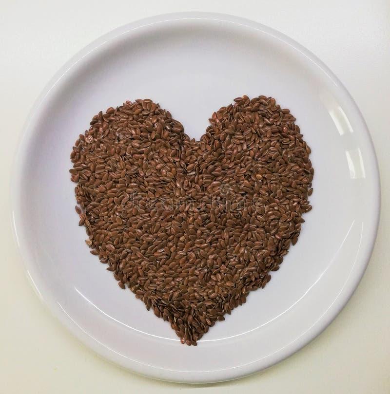 Flaxseeds de Brown sob a forma do coração fotos de stock