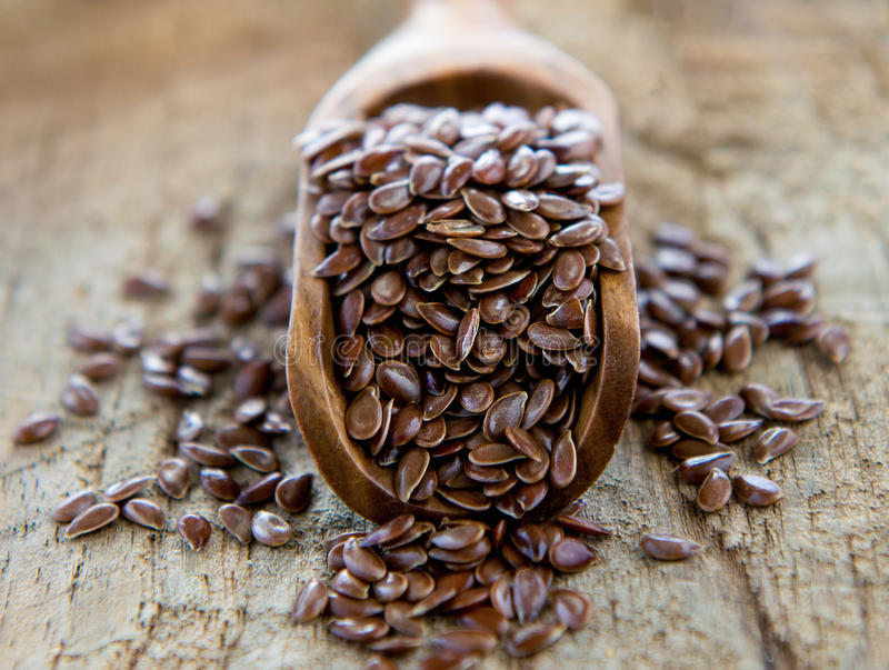 Flaxseeds in wood spoon. On wood table royalty free stock photo