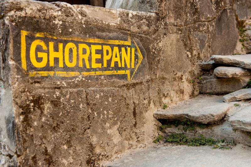 Flecha amarilla del poste indicador en la pared de piedra que dirige a Ghorepani en Poon Hill, viaje del circuito de Annapurna, N fotos de archivo