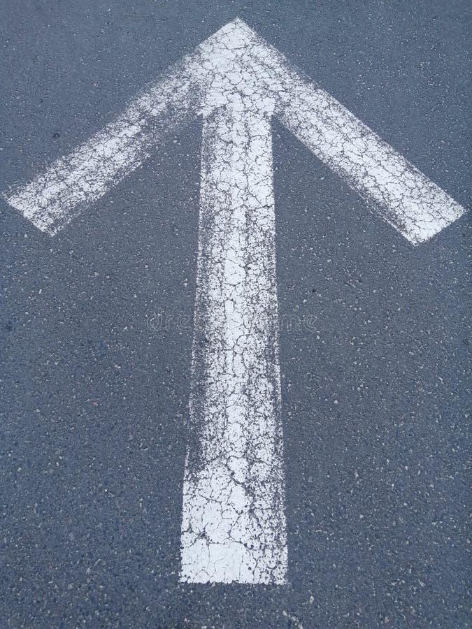 Flecha blanca Muestras delanteras en el camino Fondo gris foto de archivo