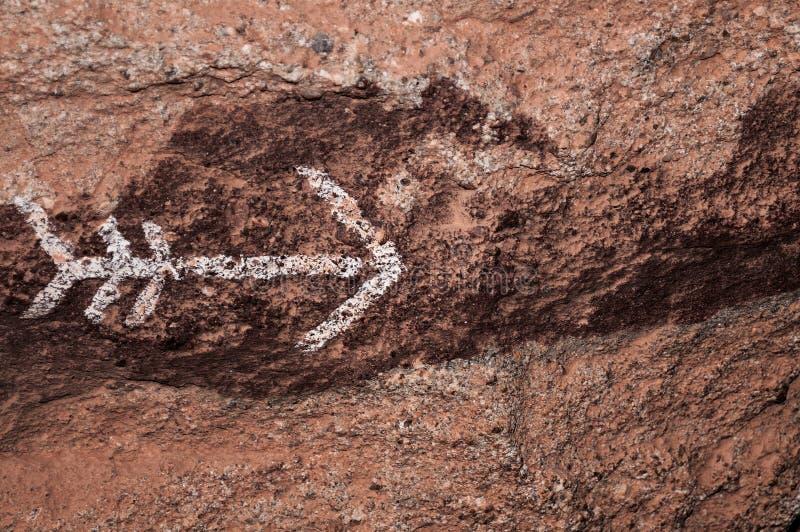 Flecha pintada en textura de la pared de la roca fotos de archivo libres de regalías