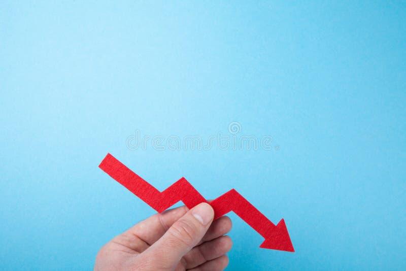 Flecha roja que cae abajo de la carta a disposición en un fondo azul Copie el espacio fotos de archivo