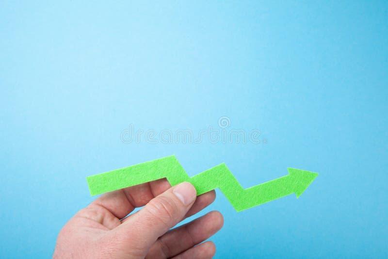 Flecha verde creciente para arriba en la mano, espacio vacío para el texto fotografía de archivo libre de regalías