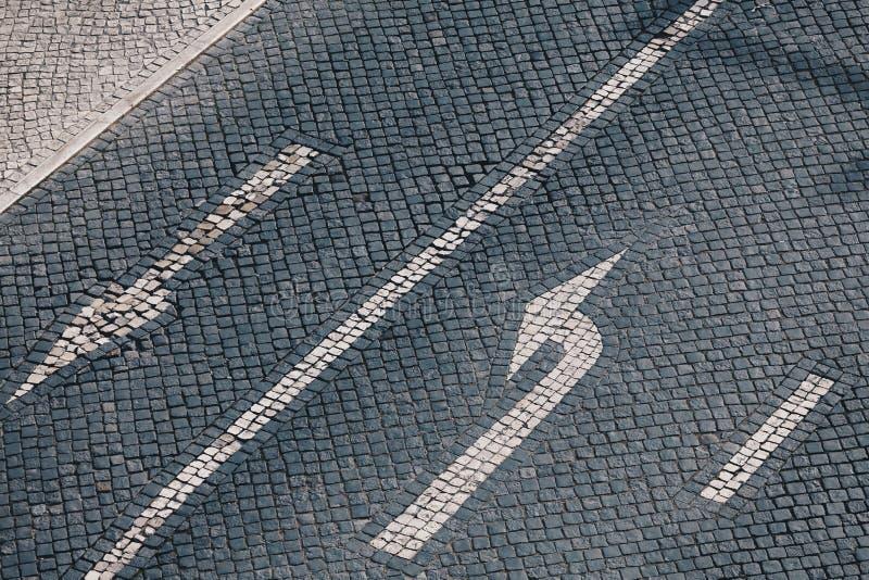 Flecha y placa de calle de la dirección en el pavimento de piedra hecho a mano en Lisboa - fondo hecho a mano portugués tradicion fotos de archivo
