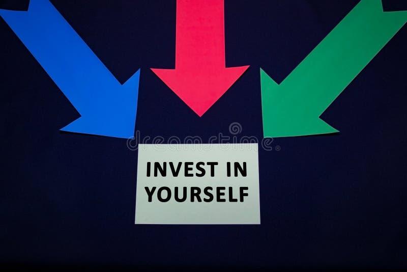 Flechas coloreadas con la etiqueta engomada de papel para el textspase en fondo azul marino Invierta en sí mismo foto de archivo