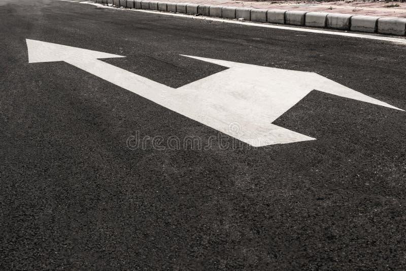 Flechas direccionales en el blacktop foto de archivo