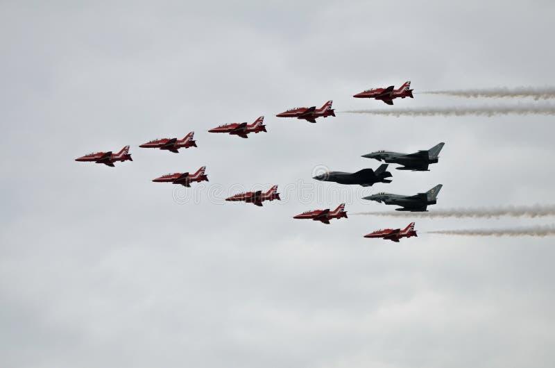Flechas, Eurofighter Typhoon y relámpago rojos F35 en la formación imagenes de archivo
