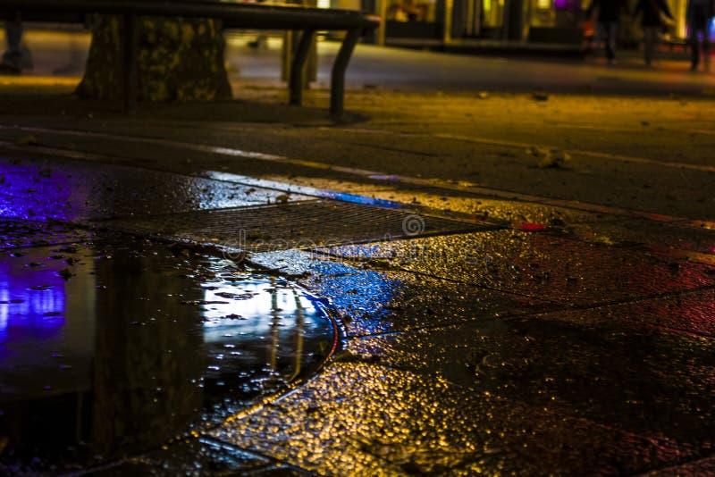 Flecken des Lichtes und der Reflexion der Feuer von der Nachtstadt in einer feuchten Fliese auf der Straße lizenzfreie stockbilder