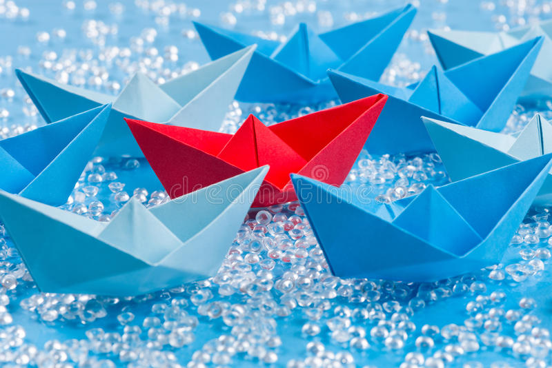 Fleet of blue Origami paper ships on blue water like background surrounding a red one royalty free stock photo
