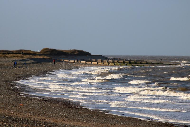 Fleetwood beach, people fishing windy January day royalty free stock photo