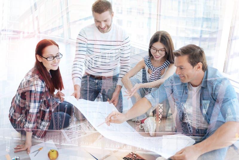 Fleißige Enthusiasten, die Unternehmensplan besprechen lizenzfreies stockbild
