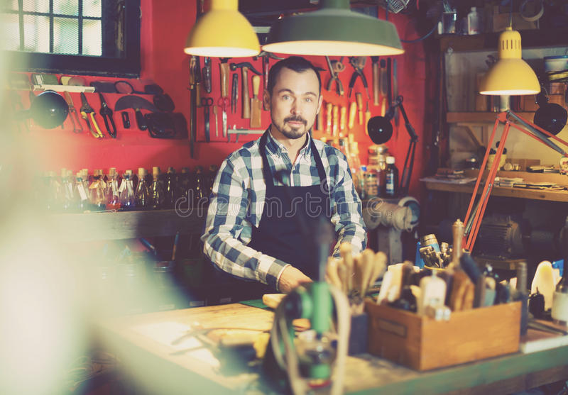 Fleißiger Mann, der seine Werkzeuge in der ledernen Werkstatt anzeigt stockfotos