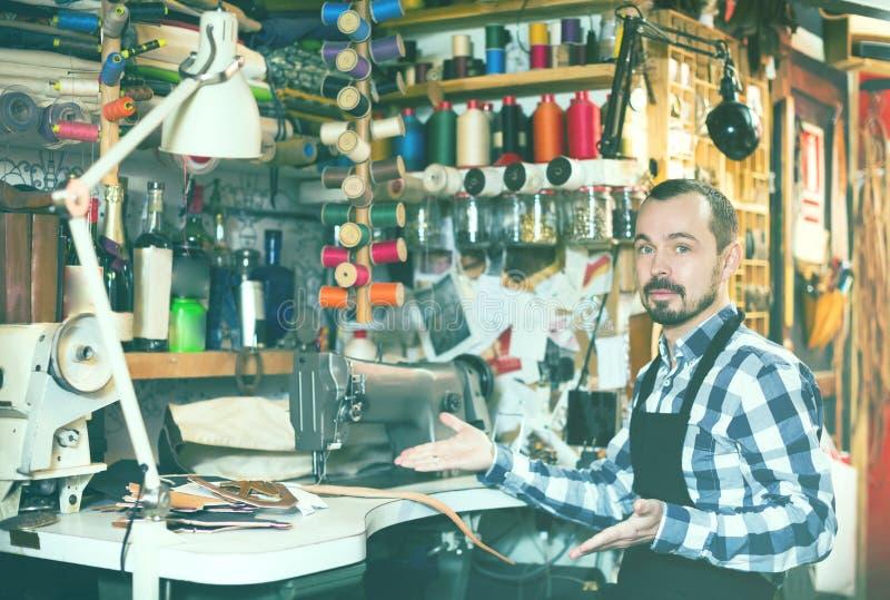 Fleißiger Mann, der seine Werkzeuge in der ledernen Werkstatt zeigt stockfotografie