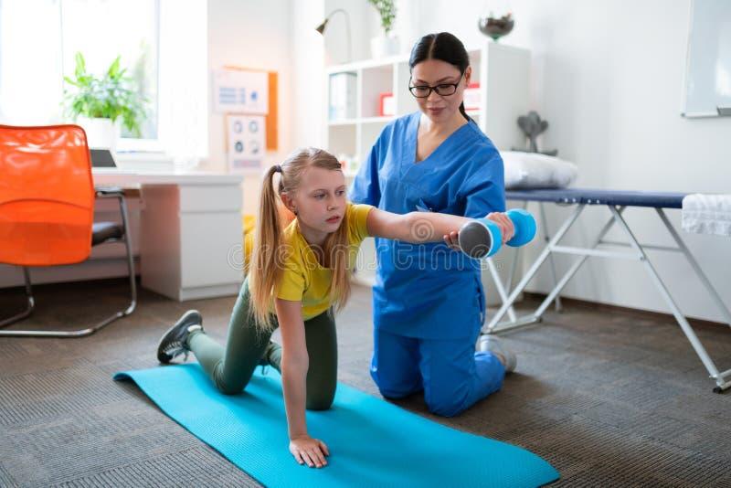 Fleißiges blondes Mädchen, das mit schweren Dummköpfen während der intensiven Rehabilitation arbeitet stockfotos