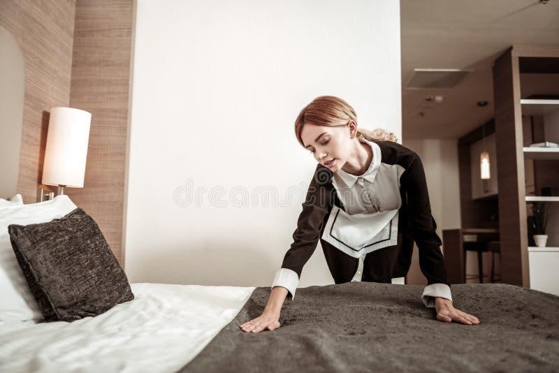 Fleißige junge Haushälterin, die morgens das Bett macht stockbild