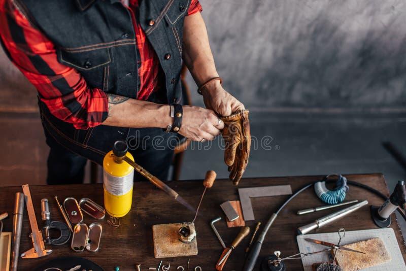 Fleißiger Mann, der auf Handschuhen outting ist, bevor das Einzelteil geschmolzen wird lizenzfreies stockfoto