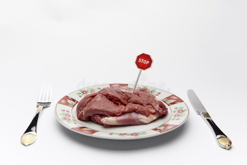 Fleisch auf einer Platte mit einem Stoppschild lizenzfreie stockfotografie