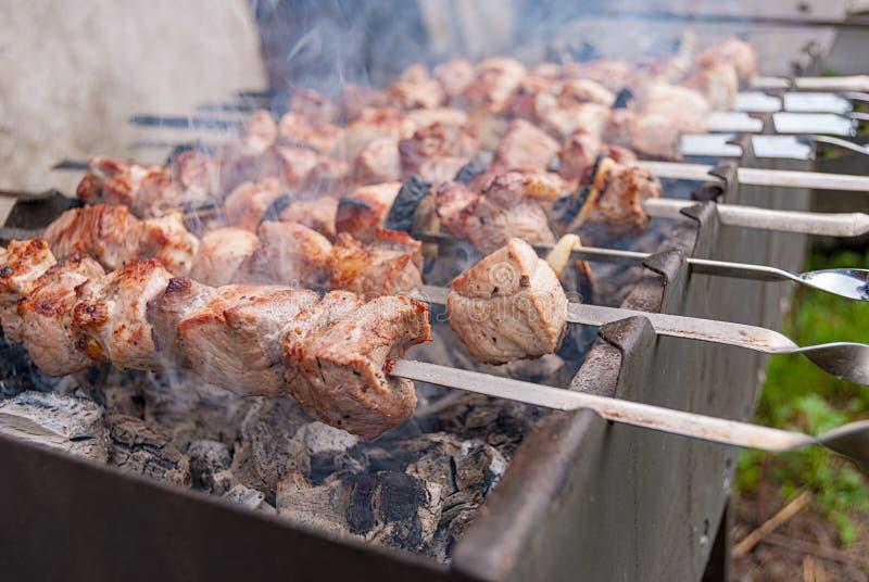 Fleisch auf Feuer in einem Metall kochend, grillen Sie stockbild