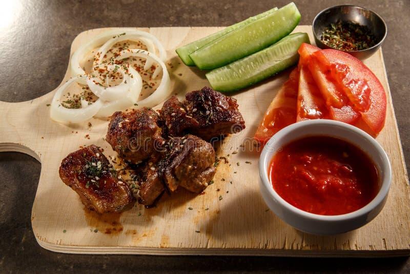 Fleisch des gebratenen Lamms mit Gewürzen, Soßen und Pfeffern auf einem rustikalen hölzernen Behälter Ansicht von oben stockfotos