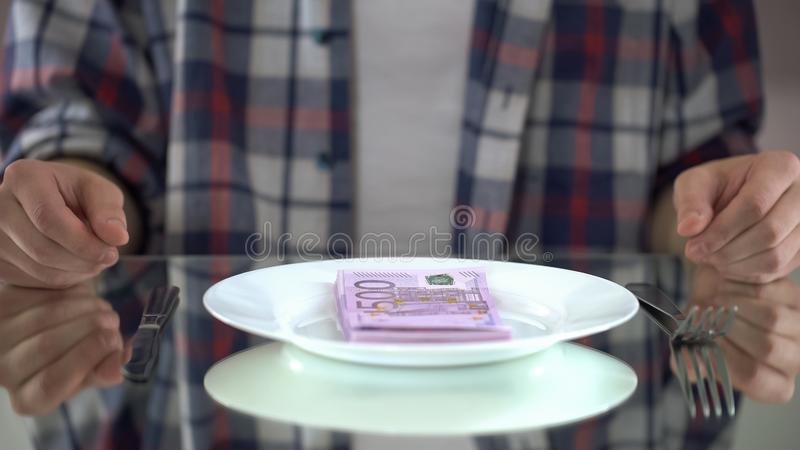 Fleisch fressende Eurobanknoten, Geld vergeudend, Symbol der Verbraucherschutzbewegung, Budget für Lebensmittel lizenzfreie stockfotos
